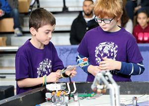 Malta Bots team members prepare their robot for a mission at FLL Competition